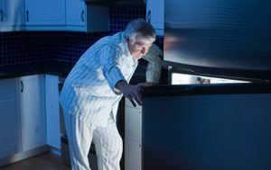 Senior man looking in refrigerator at night